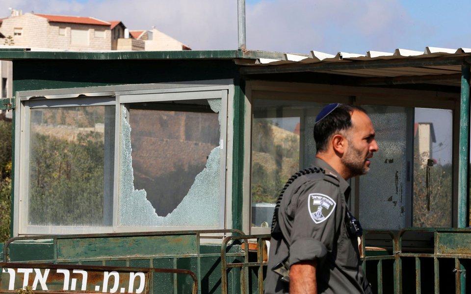 Policial israelense passa por posto de controle danificado depois que palestino deixou três guardas israelenses mortos em assentamento judeu, na Cisjordânia ocupada 26/09/2017 REUTERS/Ammar Awad