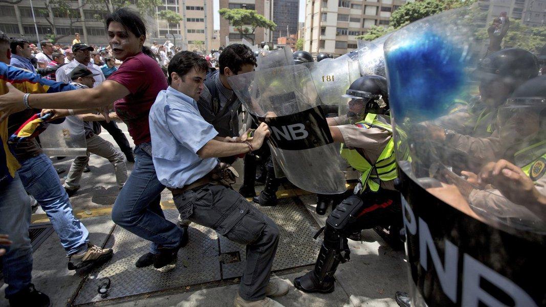 Manifestantes e polícia se enfrentam durante protestos contra o governo de Nicolás Maduro, em Caracas, Venezuela