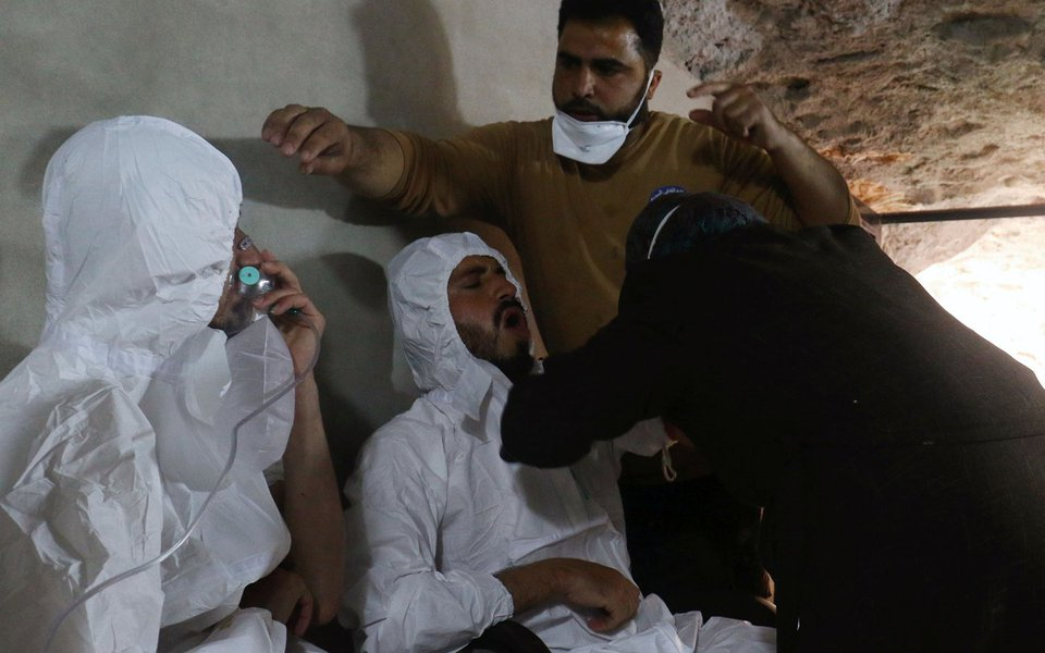 Homem respira com máscara de oxigênio e outro recebe tratamento, após suspeito ataque de gás na cidade de Khan Sheikhoun, na Síria. Síria 04/04/2017 REUTERS/Ammar Abdullah