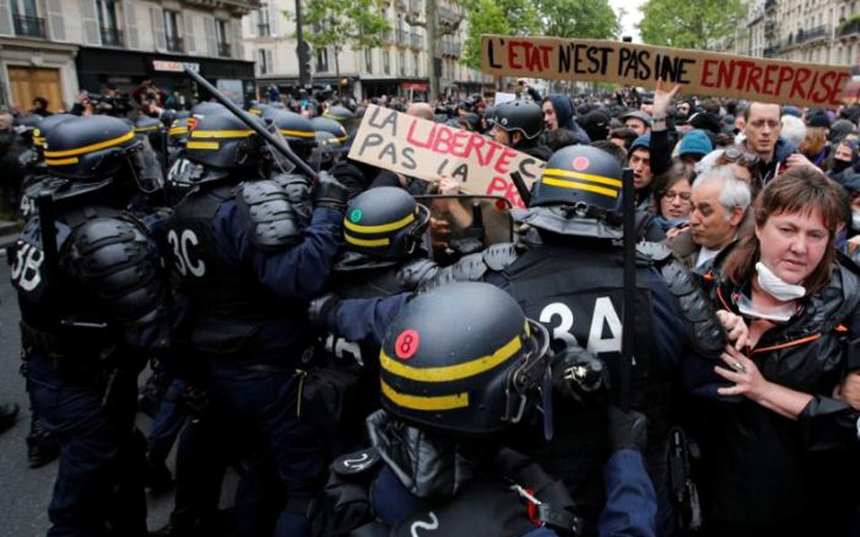 French riot police surround demonstrators who hold a placard with the message, 'The State is not an Company', the day after the country went to the polls, in Paris, France, May 8, 2017.REUTERS/Jean-Paul Pelissier
