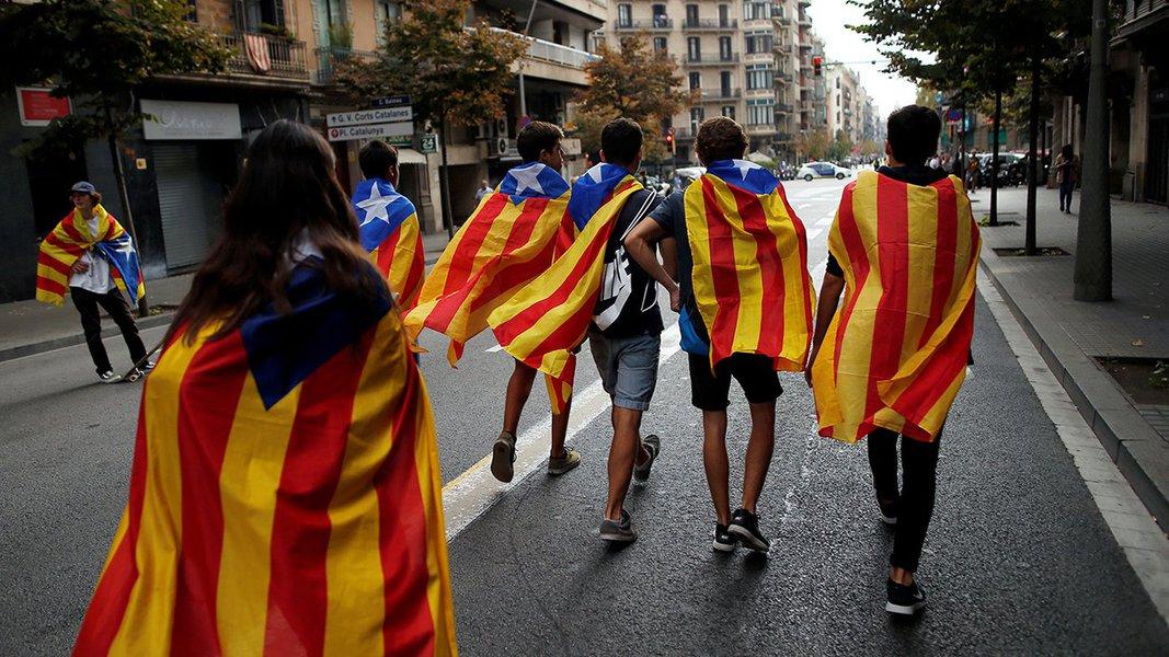 Jovens enrolados em bandeiras separatistas da Catalunha caminham durante protesto em Barcelona 03/10/2017 REUTERS/Jon Nazca
