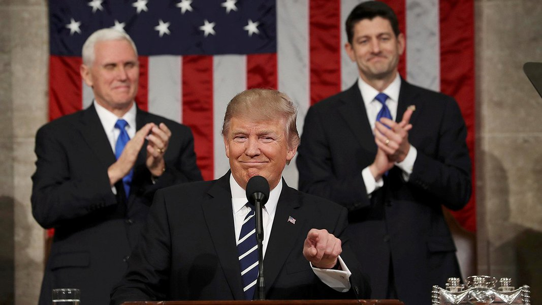 US Vice President Mike Pence (L) and Speaker of the House Paul Ryan (R) applaud as US President Donald J. Trump (C) arrives to deliver his first address to a joint session of Congress from the floor of the House of Representatives in