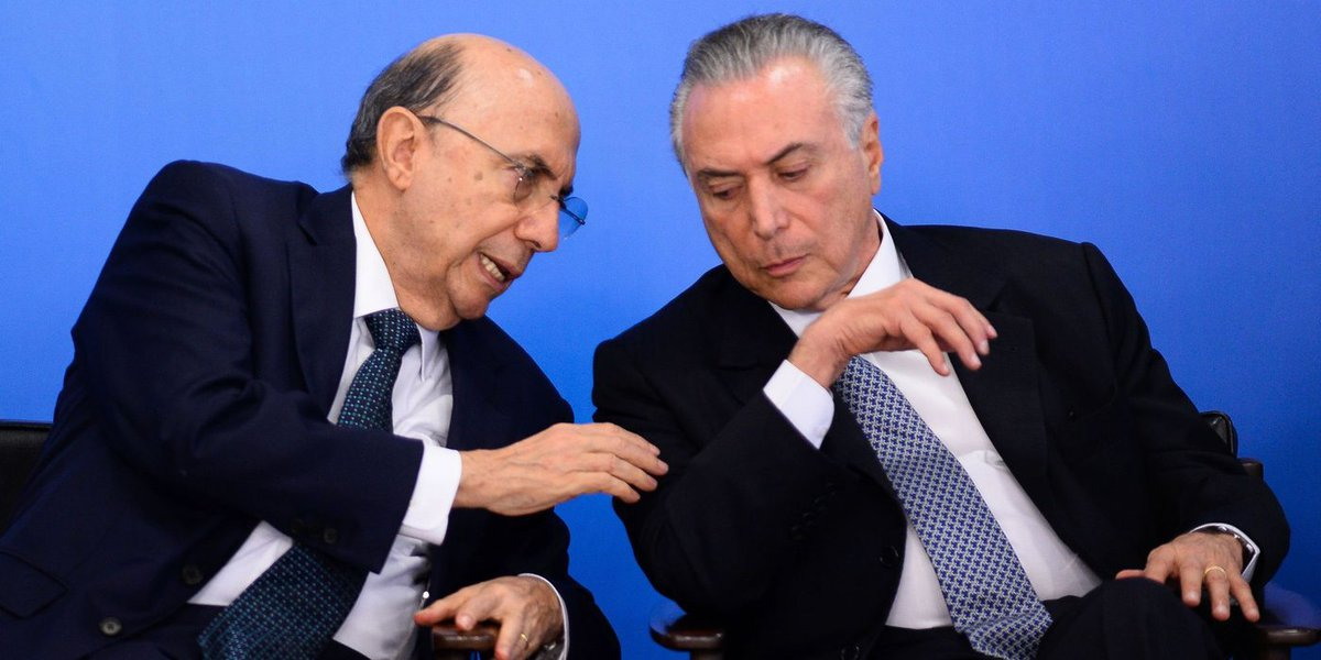 Brazilian Finance Minister Henrique Meirelles (L) and acting President Michel Temer attend a meeting