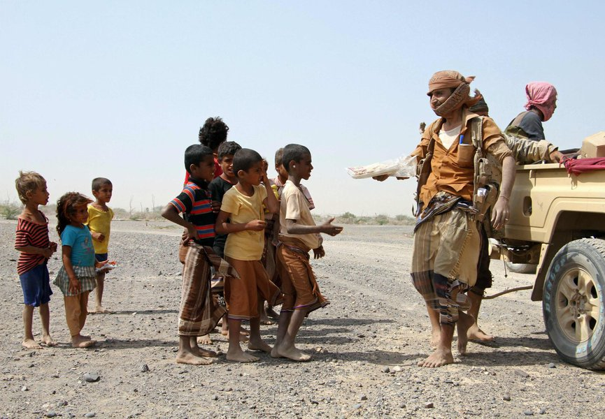 Pro-government fighters give food to Yemeni children on the road leading to the southwestern port city of Mokha on January 26, 2017. Yemeni rebels are putting up fierce resistance in a key Red Sea