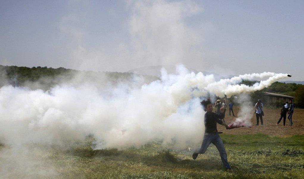 Imigrante arremessando lata de gás lacrimogêneo atirada pela polícia no vilarejo de Idomeni, na fronteira entre Grécia e Macedônia. 13/04/2016 REUTERS/Stoyan Nenov