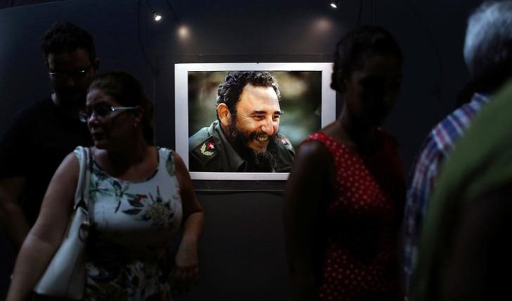 "People look at a picture of Cuba's former President Fidel Castro during the opening of the exhibition ""Fidel"" in Havana, Cuba, August 12, 2016. REUTERS/Alexandre Meneghini"