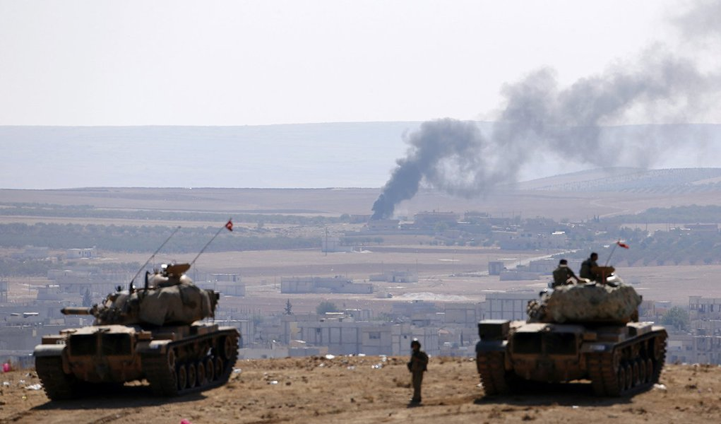 Smoke rises from the Syrian town of Kobani, Turkish army tanks take position on the Turkish