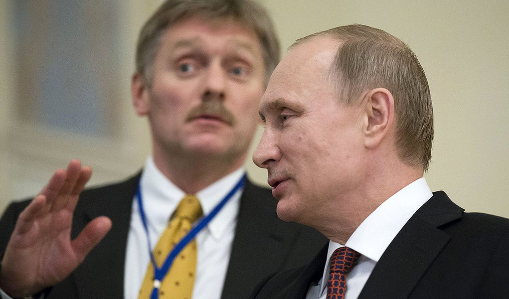 In this photo taken on Thursday, Feb.  12, 2015, Russian President Vladimir Putin,  right, speaks to a journalist as his press secretory  Dmitry Peskov tries to stop questions after the peace talks in Minsk, Belarus, Thursday, Feb. 12, 2015.  Peskov told