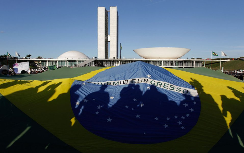 Demonstrators open a Brazil's flag in front of the National Congress during a protest in Brasilia, Brazil, Wednesday, June 26, 2013. The wave of protests that hit Brazil on June 17 began as opposition to transportation fare hikes, then expanded to a list