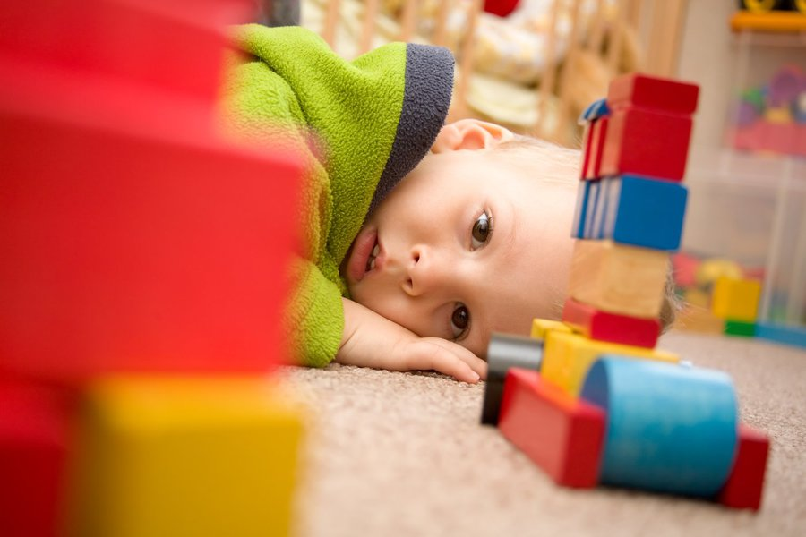 Sick boy is among the toys on the floor.