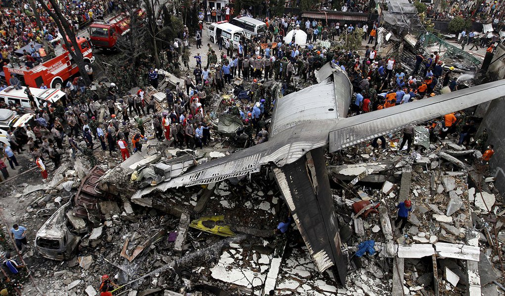 Forças de segurança examinando os destroços da aeronave C-130 Hercules, na cidade de Medan, na Indonésia. 30/06/2015 REUTERS/Roni Bintang