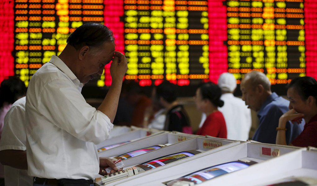 Investors look at computer screens showing stock information at a brokerage house in Shanghai, China 