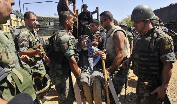 Soldados libaneses ajudam refugiados síria a se retirarem de Arsal, cidade na fronteira com a Síria.  4/08/2014. REUTERS/Hassan Abdallah