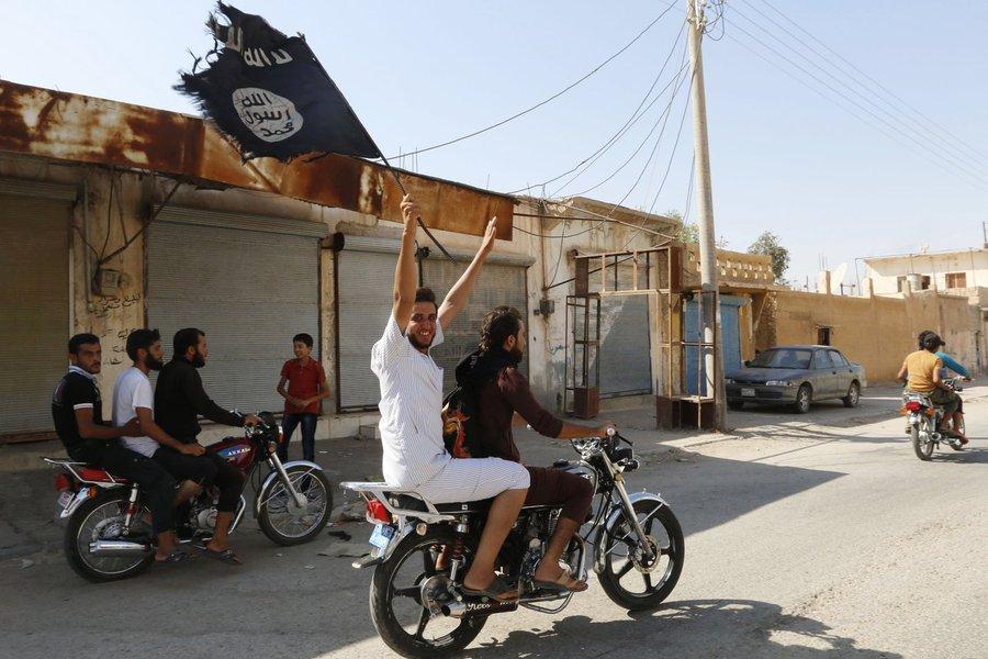 Moradores de Tabqa erguem bandeira do Estado Islâmico perto de Raqqa. 24/08/2014 REUTERS/Stringer