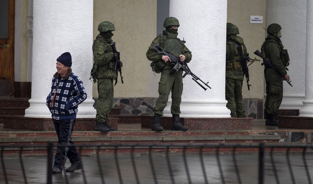 Armed men stand guard at the Simferopol airport in the Crimea region February 28, 2014. Armed men took control of two airports in the Crimea region on Friday in what Ukraine's government described as an invasion and occupation by Russian forces, raising t