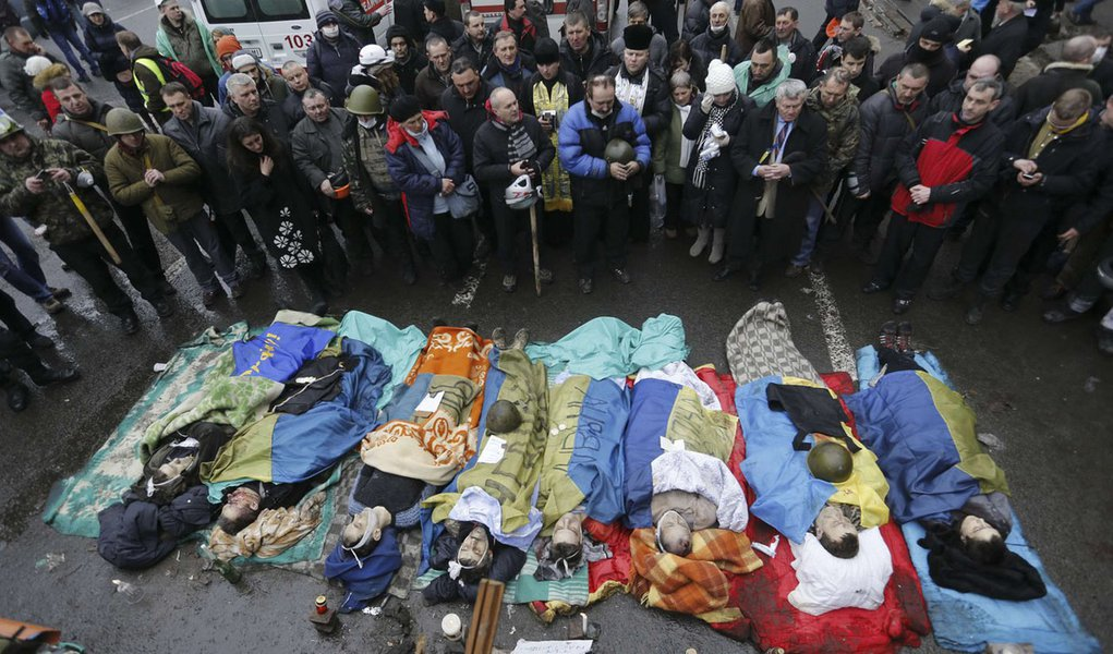 ATTENTION EDITORS - VISUAL COVERAGE OF SCENES OF INJURY OR DEATH  People pray near the bodies of anti-government protesters killed during clashes with riot police in Kiev February 20, 2014. Ukraine suffered its bloodiest day since Soviet times on Thursd