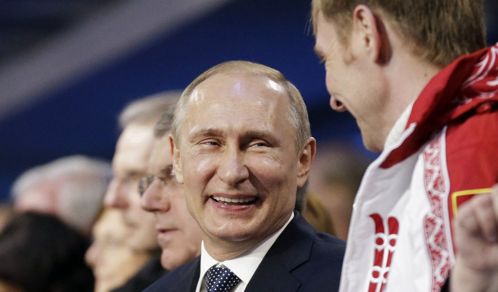 Russian President Vladimir Putin (L) laughs with Russia's gold medallist bobsleigh athlete Alexander Zubkov during the closing ceremony for the 2014 Sochi Winter Olympics, February 23, 2014.            REUTERS/David Goldman/Pool (RUSSIA  - Tags: OLYMPICS