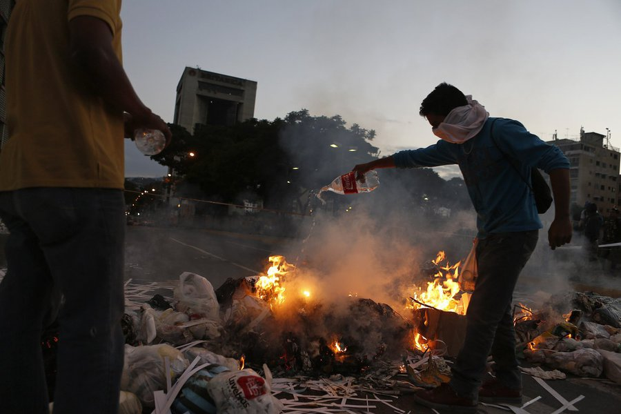 Opposition supporters stand near a burning barricade at Altamira square in Caracas February 20, 2014. Venezuelan security forces and demonstrators faced off in streets blocked by burning barricades in several provincial cities on Thursday as protests esca