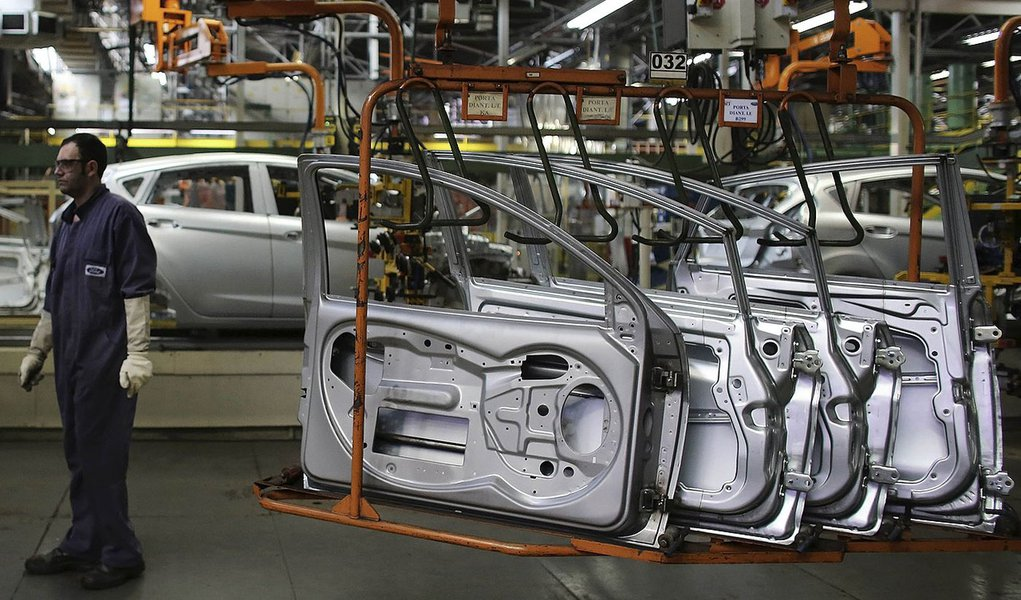 A Brazilian worker stands next to doors of a Ford car on a assembly line at Sao Bernardo do Campo Ford plant, near Sao Paulo August 13, 2013. The pace of vehicle production in Brazil slipped in July to the lowest daily rate in five months as factories, fa