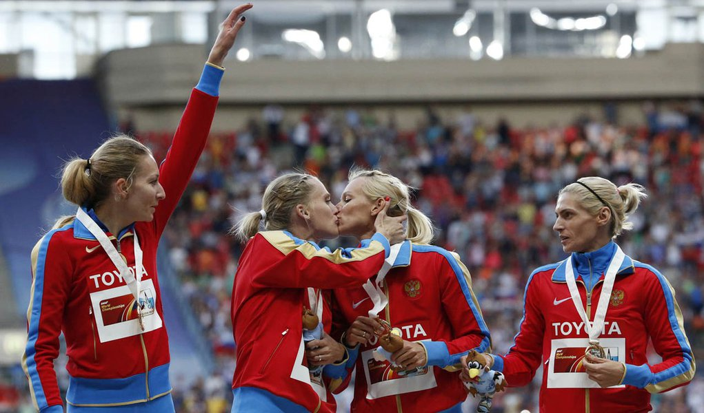 Gold medallists team Russia kiss and celebrate at the women's 4x400 metres relay victory ceremony during the IAAF World Athletics Championships at the Luzhniki stadium in Moscow August 17, 2013. From left: Yulia Gushchina, Kseniya Ryzhova, Tatyana Firova