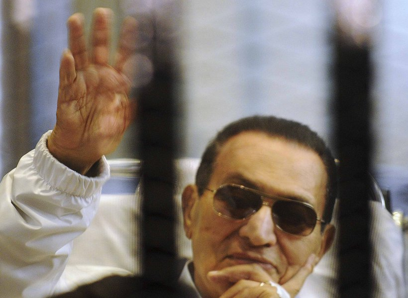 Former Egyptian President Hosni Mubarak waves to his supporters inside a cage in a courtroom at the police academy in Cairo April 13, 2013. The retrial of former Egyptian President Hosni Mubarak was aborted on Saturday when the presiding judge withdrew fr