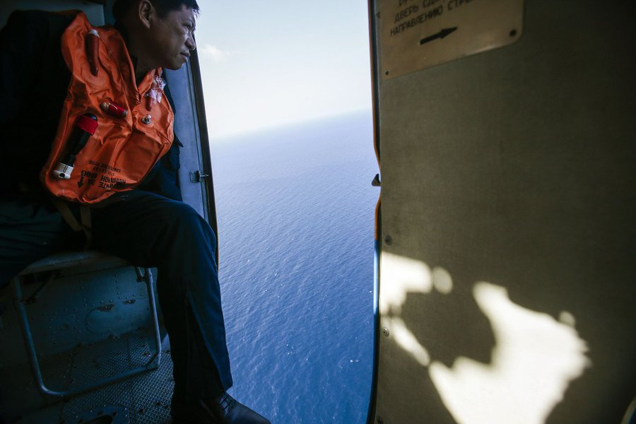 """A military personnel looks out of a helicopter during a search and rescue mission off Vietnam's Tho Chu island March 10, 2014. The disappearance of Malaysia Airlines flight MH370, a Boeing 777-200ER jetliner, is an """"unprecedented mystery"""", the country's c"""