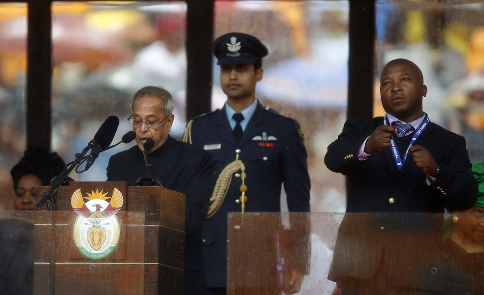 India's President Pranab Mukherjee speaks at the podium as a sign language interpreter (R) punches the air beside him during a memorial service for late South African President Nelson Mandela at the FNB soccer stadium in Johannesburg December 10, 2013. Th