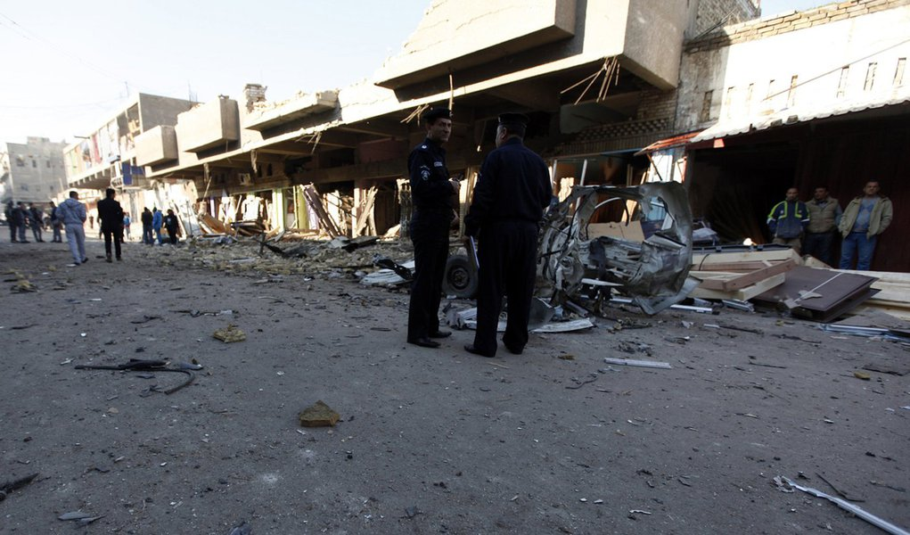 Iraqi policemen inspect the site of car bomb attack in Baghdad December 16, 2013. A series of suicide bombings and car and roadside bombs across Iraq killed at least 17 people on Monday, medical and police sources said. REUTERS/Ahmed Saad (IRAQ - Tags: CI