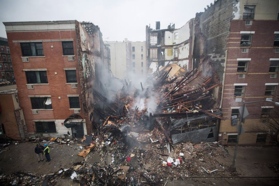 New York City firefighters work at the site of a building explosion and collapse in the Harlem section of New York, March 12, 2014. Two New York City buildings collapsed on Wednesday in an explosion believed to be caused by a gas leak, killing two people,