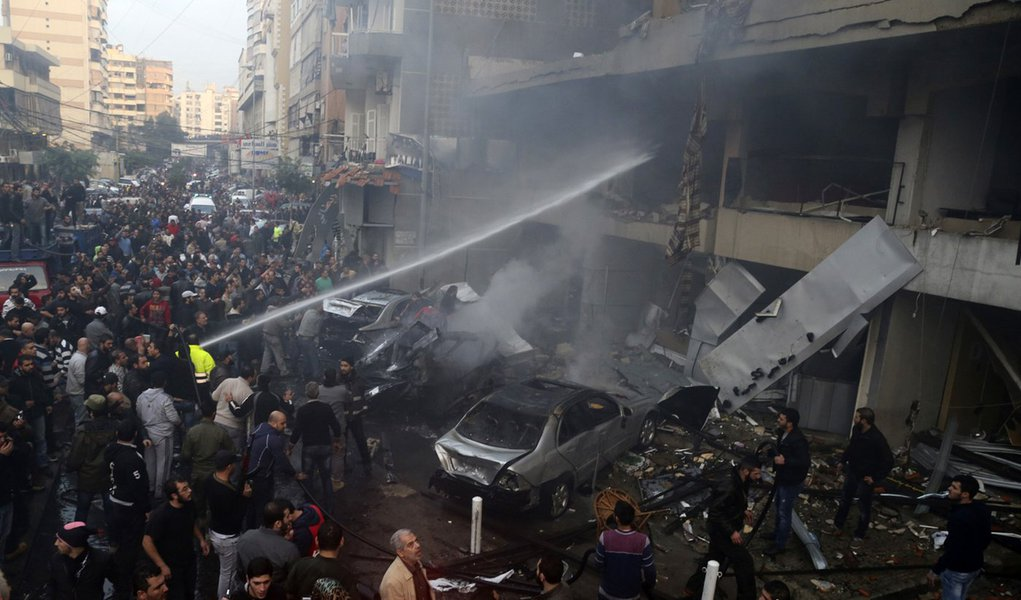 People gather as firefighters attempt to extinguish a fire at the site of an explosion in Beirut's southern suburbs, January 2, 2014. A car bomb killed four people in Hezbollah's southern Beirut stronghold on Thursday, security and medical sources said, t