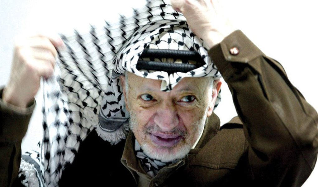 (FILES) This file photo dated 12 April 2...RAMALLAH, -:  (FILES) This file photo dated 12 April 2003 shows Palestinian leader Yasser Arafat adjusting his head-dress, keffiyeh, during a meeting in his Ramallah office. It was announced 11 November 2004 that