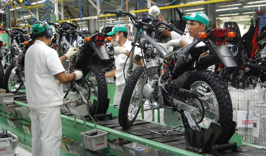 Operários da Honda trabalham em linha de montagem de motocicleta na Zona Franca de Manaus, AM, um dos principais polos industriais do Brasil.
