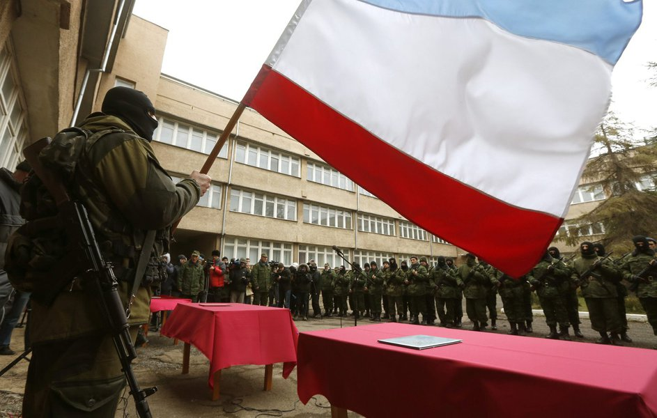 An armed man, believed to be a Russian serviceman, holds a Crimea flag as members of a pro-Russian self defence unit stand in a formation before taking an oath to Crimea government in Simferopol March 10, 2014. Russian forces consolidated their hold on Uk