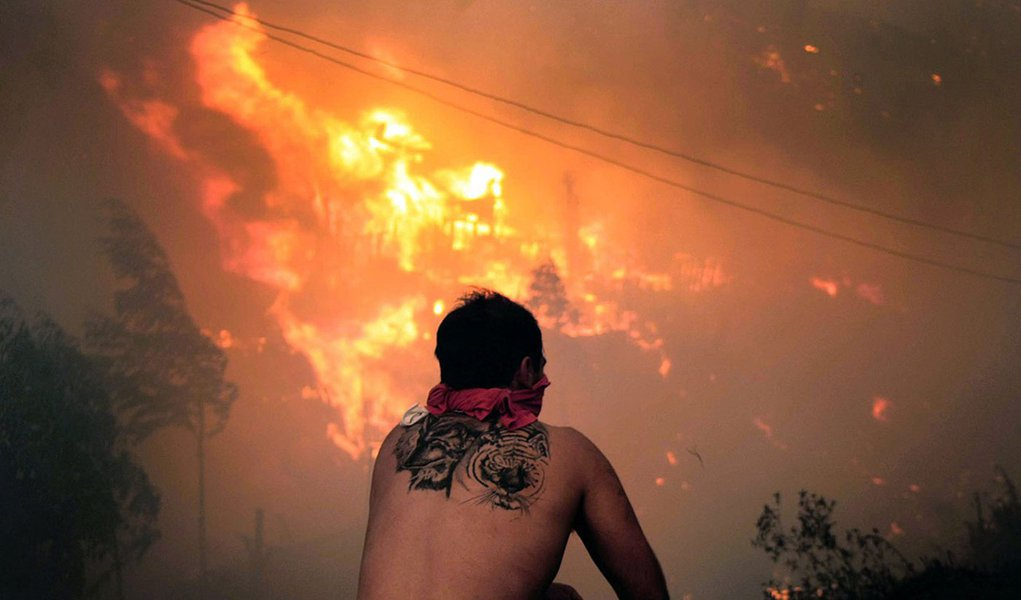 A local stares at houses in flames during a fire in Valparaiso, 110 km west of Santiago, Chile, on April 12, 2014. Authorities decreed a red alert for the area after the fire consumed more than 100 houses.   AFP PHOTO / FELIPE GAMBOA
