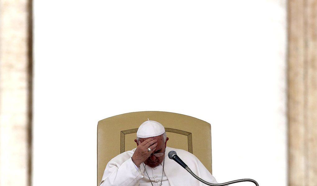 Pope Francis touches his forehead as he leads the general audience in Saint Peter's square at the Vatican April 9, 2014. REUTERS/Alessandro Bianchi   (VATICAN - Tags: RELIGION)