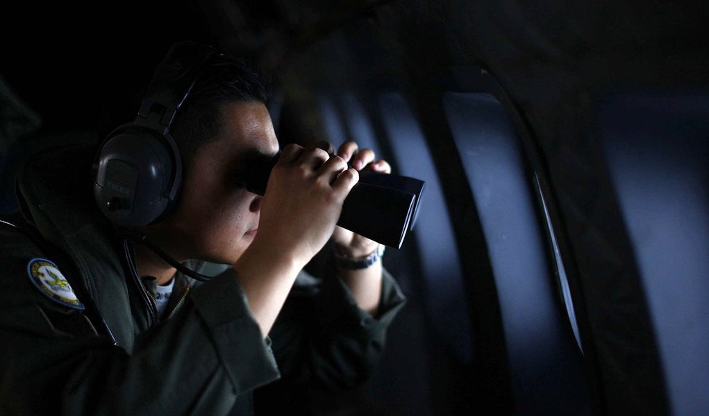 A crew member from the Royal Malaysian Air Force uses binoculars onboard a Malaysian Air Force CN235 aircraft during a Search and Rescue (SAR) operation to find the missing Malaysia Airlines flight MH370, in the Straits of Malacca March 13, 2014. REUTERS/
