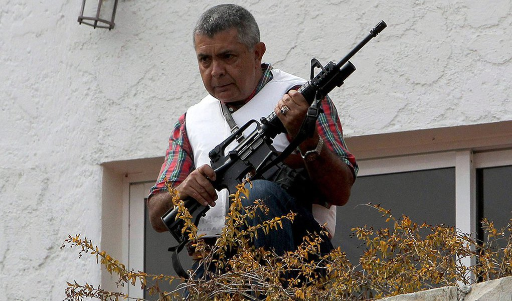 Angel Vivas, a retired army general and anti-Maduro protester, stands in his house with an automatic weapon as he resists be detained in Caracas February 23, 2014. According to local media, President Nicolas Maduro ordered the detention of Vivas on Saturd