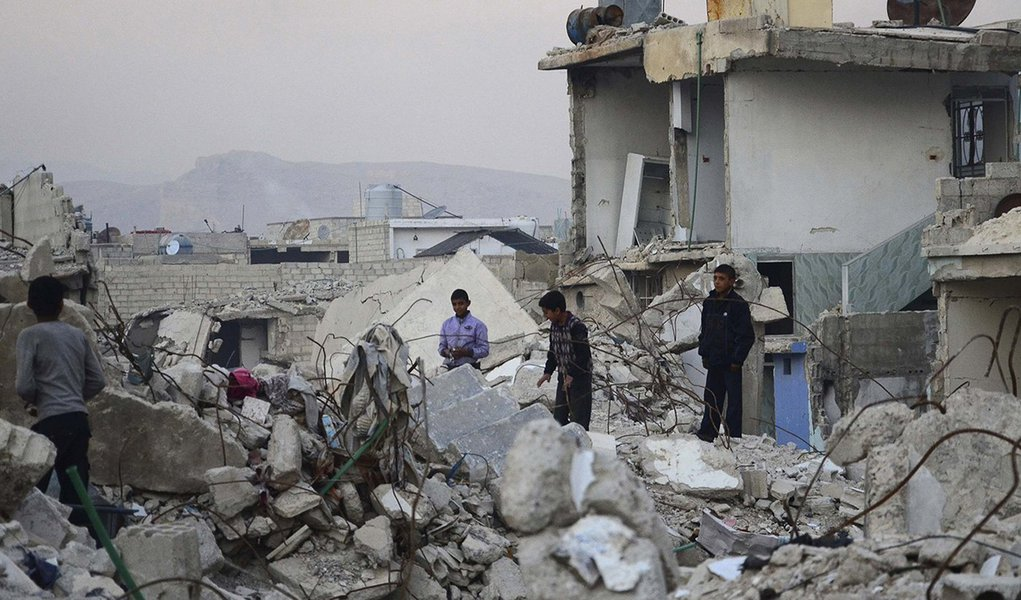 Children walk on rubble of damaged buildings in the Duma neighbourhood of Damascus December 2, 2013. Picture taken December 2, 2013. REUTERS/Yousef Albostany (SYRIA - Tags: POLITICS CIVIL UNREST CONFLICT)