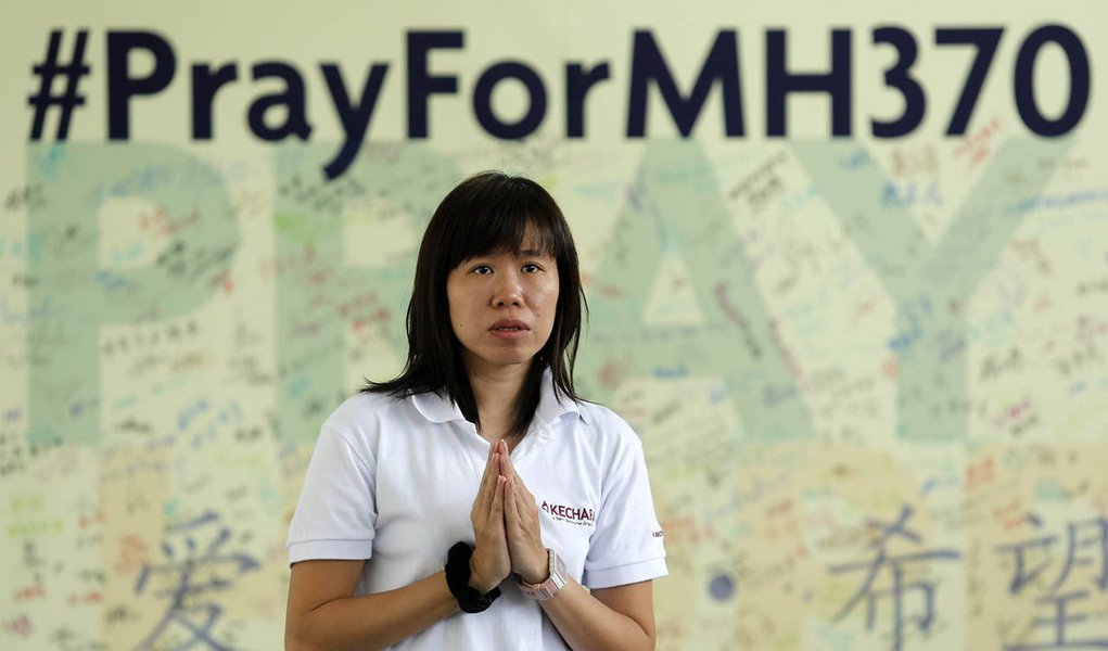 A woman prays for passengers onboard the missing Malaysia Airlines flight MH370 at Kechara retreat centre in Bentong outside Kuala Lumpur April 13, 2014. The search for the missing jetliner resumed on Saturday, five weeks after the plane disappeared from