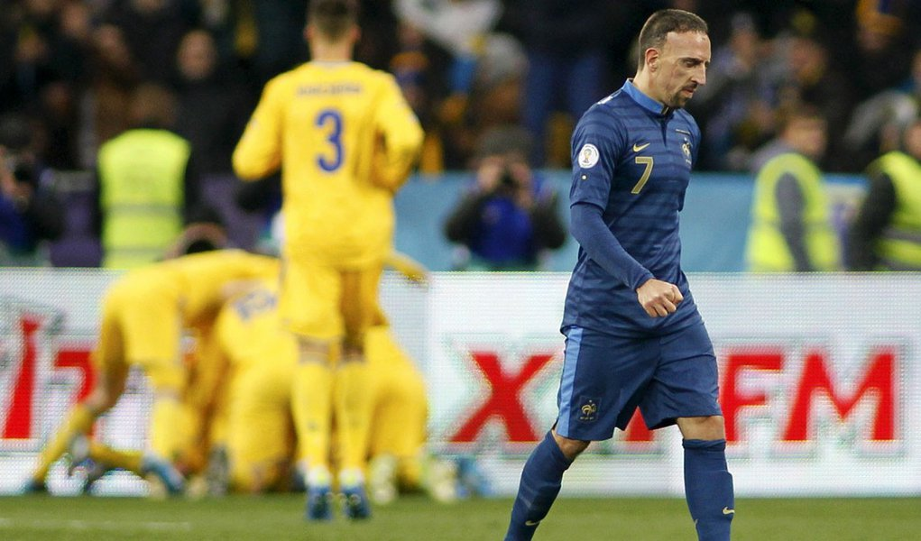 France's Franck Ribery (front) walks after Ukraine's Andriy Yarmolenko celebrates his goal with team mates (back) during the 2014 World Cup qualifying first leg playoff soccer match at the Olympic stadium in Kiev November 15, 2013.  REUTERS/Gleb Garanich