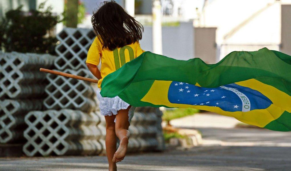 SÃO PAULO (SP) - BRASIL - 12-06-2014 - COPA DO MUNDO 2014 - Perto do momento da Abertura da Copa do Mundo 2014, menina corre com a bandeira do Brasil em rua de Osasco, Grande São Paulo.- (Foto: Chico Cardillo/FOTOS PÚBLICAS)