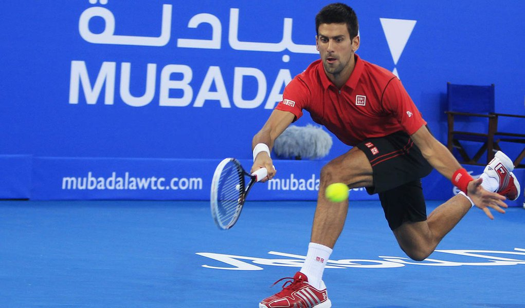Novak Djokovic of Serbia hits a return to David Ferrer of Spain during their final tennis match at  Mubadala World Tennis Championship in Abu Dhabi December 28, 2013. REUTERS/Rula Rouhana (UNITED ARAB EMIRATES - Tags: SPORT TENNIS)