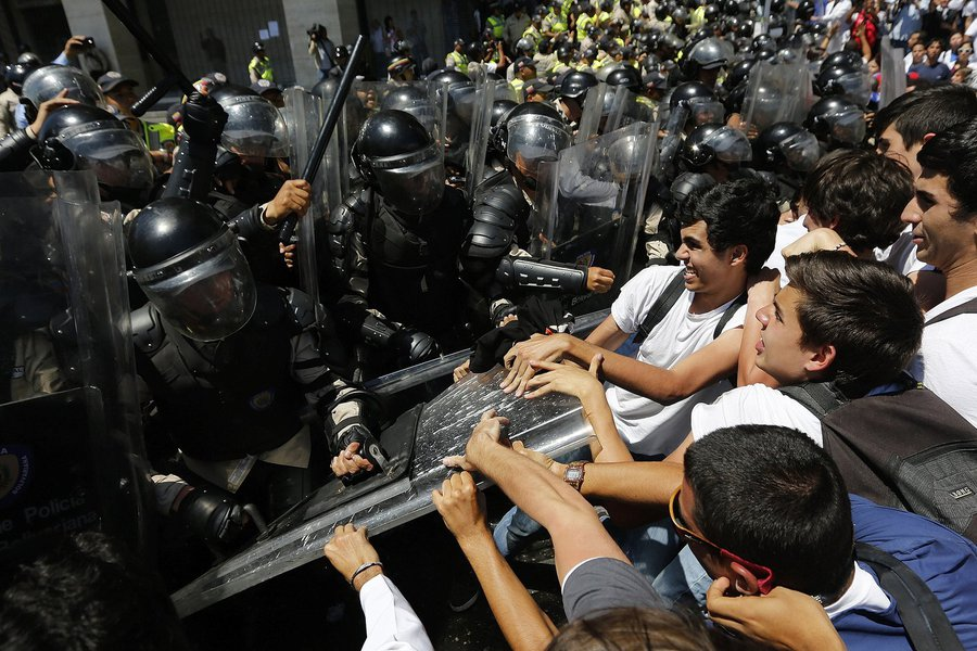Anti-government medical students scuffle with national policemen during a march demanding medical supplies for hospitals in Caracas March 10, 2014. As violent protests in Venezuela alienate moderates in the opposition and show no signs of toppling Preside