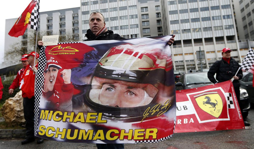 Philippe, a fan from Lyon, waves a flag as he attends a silent 45th birthday tribute to seven-times former Formula One world champion Michael Schumacher with Ferrari fans in front of the CHU hospital emergency unit in Grenoble, French Alps, where Michael
