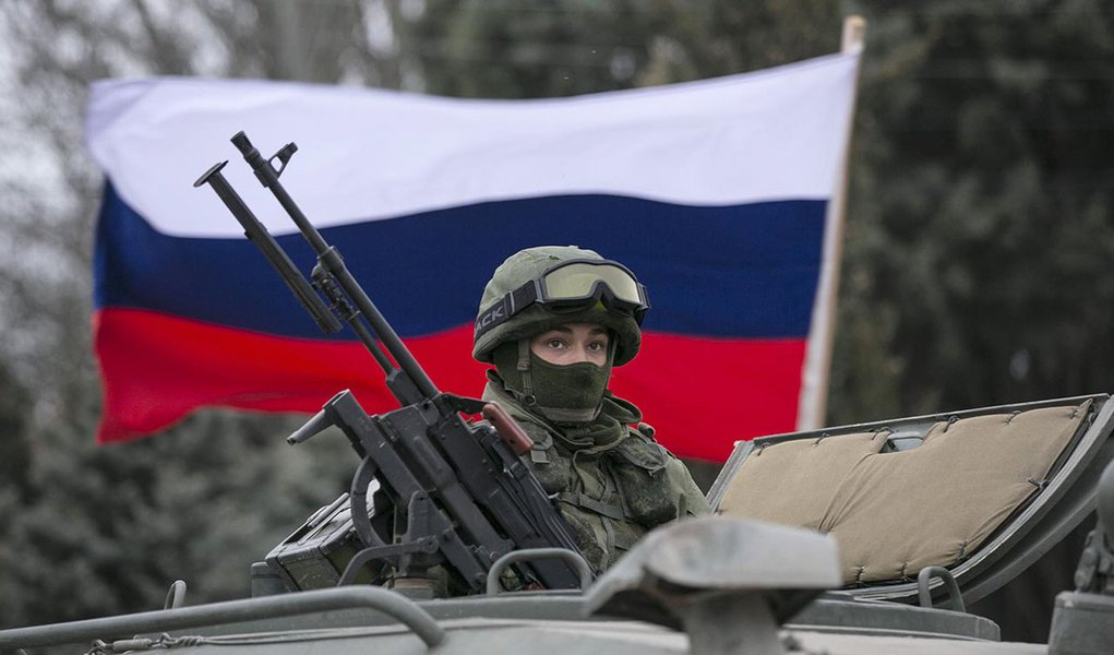 A pro-Russian man (not seen) holds a Russian flag behind an armed servicemen on top of a Russian army vehicle outside a Ukrainian border guard post in the Crimean town of Balaclava March 1, 2014. Ukraine accused Russia on Saturday of sending thousands of