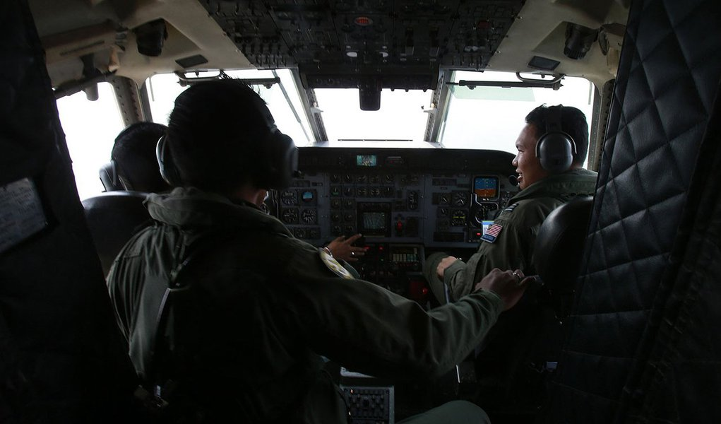 Royal Malaysian Air Force pilots work in the cockpit of a Malaysian Air Force CN235 aircraft during a Search and Rescue (SAR) operation to find the missing Malaysia Airlines flight MH370, in the Straits of Malacca March 13, 2014. REUTERS/Samsul Said (MALA