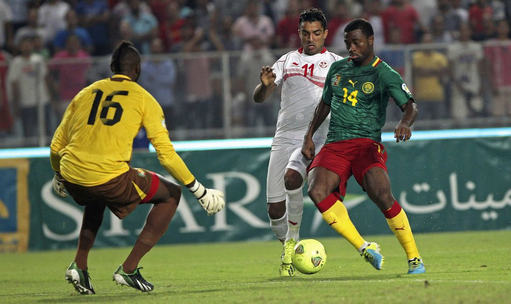Tunisia's Sami Allagui (C) fights for the ball with Cameroon's Aurelien Chedjou (R) during their 2014 World Cup qualifying soccer match at Rades Stadium in Tunis October 13, 2013 . REUTERS/Zoubeir Souissi (TUNISIA - Tags: SPORT SOCCER)