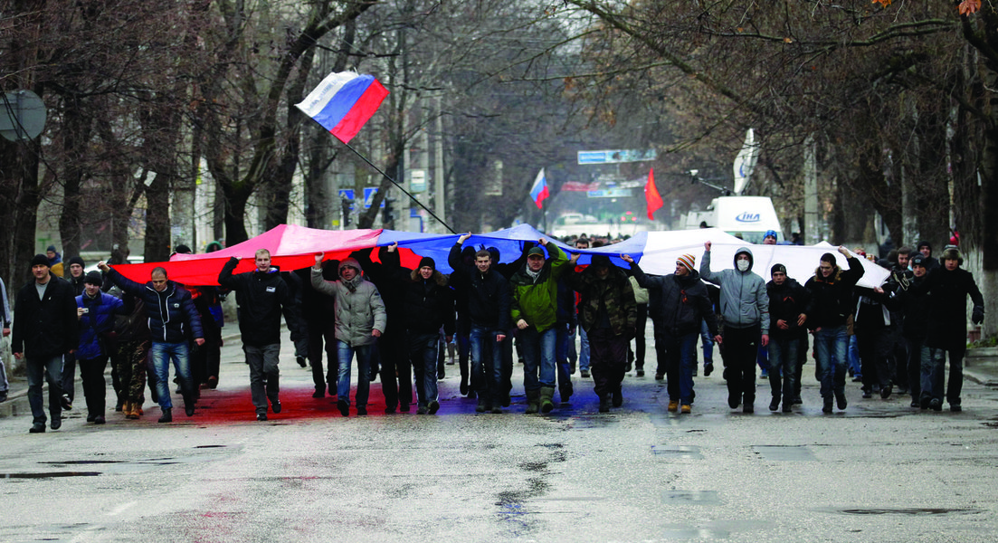 Pro-Russian demonstrators march with a huge Russian flag during a protest in front of a local government building in Simferopol, Crimea, Ukraine, Thursday, Feb. 27, 2014. Ukraine's acting interior minister says Interior Ministry troops and police have bee