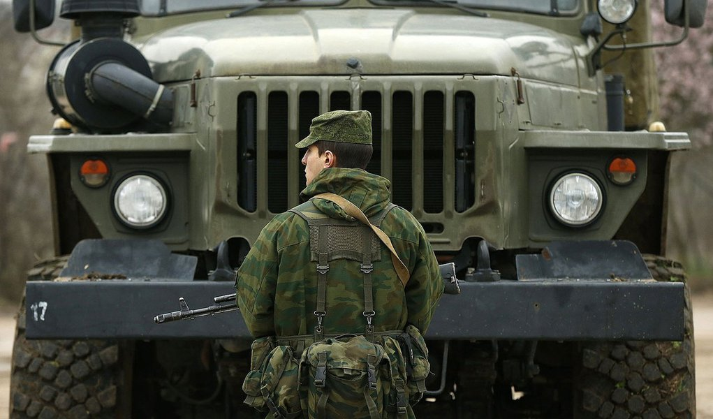A uniformed man, believed to be a Russian serviceman, stands guard near a Ukrainian military base outside the city of Sevastopol, March 7, 2014. President Vladimir Putin rebuffed a warning from U.S. President Barack Obama over Moscow's military interventi