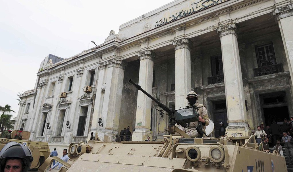 Egyptian soldiers and police officers stand guard with armoured personnel carriers (APC) outside the criminal court in the Mediterranean city of Alexandria, 220 km (137 miles) northwest of Cairo, March 3, 2014. Two Egyptian policemen were sentenced to 10